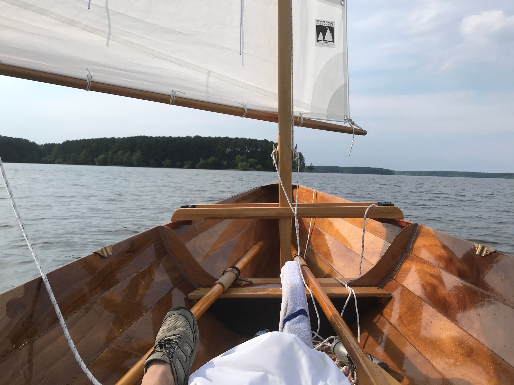 Picture of the bow of a sailboat, with sail, oars, and foot in view